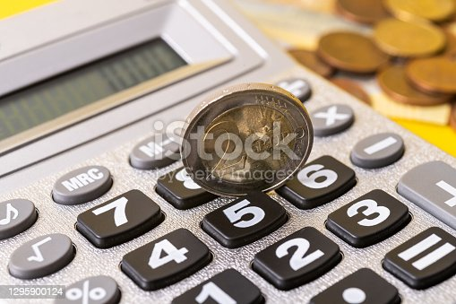 A two-euro coin stands on the edge of the calculator panel