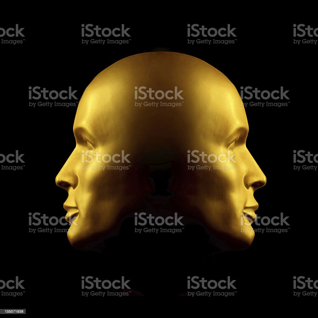Two-faced gold head statue stock photo
