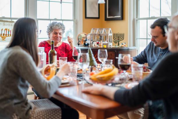 dwupokoleniowa wielokulturowa rodzina, starsza para z dorosłymi dziećmi, zebrała się razem i zjeżdj świąteczny obiad w salonie urządzonym zarówno na boże narodzenie, jak i chanukę. - judaizm zdjęcia i obrazy z banku zdjęć