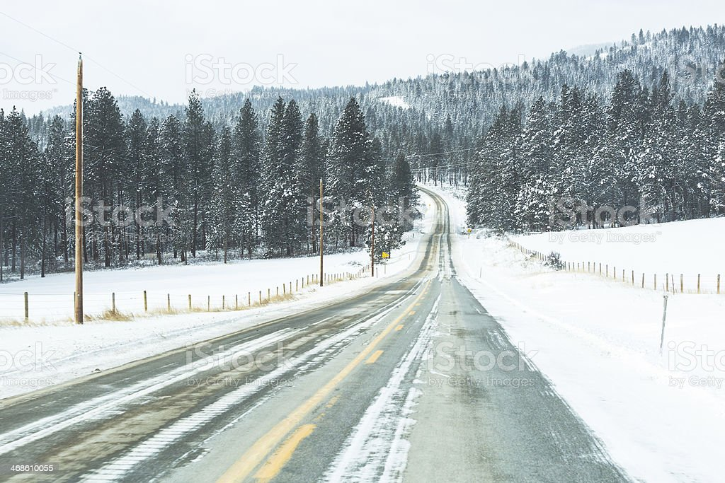 Two-Lane Highway Snowpacked & Icy Montana Mountains Forest royalty-free stock photo