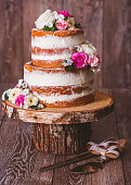 Homemade two-layered wedding naked cake decorated with flowers on a wooden cut stand