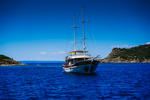 A two-masted yacht is anchored in the bay of the sea, ocean, lake. Rest on a yacht. Sailing. Vacation on a sea yacht. Mediterranean summer landscape. Seasickness.
