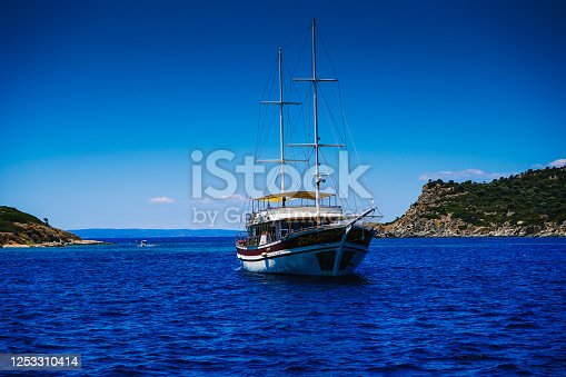 1066331604 istock photo A two-masted yacht is anchored in the bay of the sea, ocean, lake. Rest on a yacht. Sailing. Vacation on a sea yacht. Mediterranean summer landscape. Seasickness. 1253310414