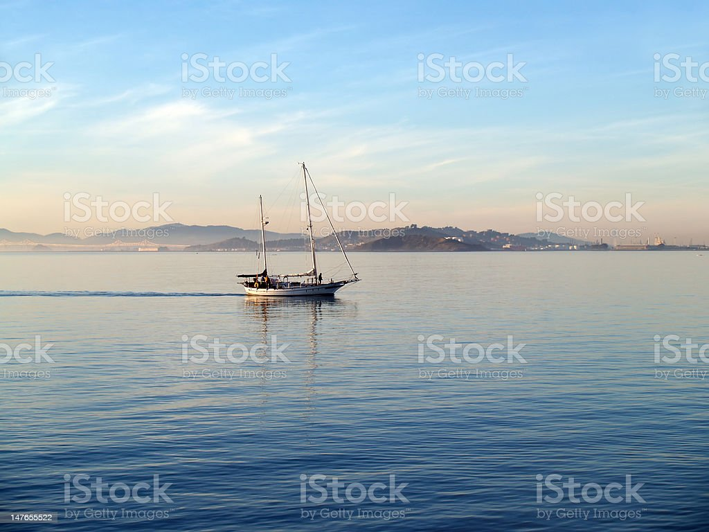 two-masted yacht motoring across still water stock photo