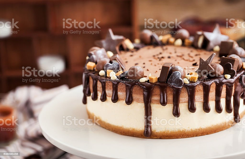 Two-ply chocolate cheesecake decorated with candies and frosting - foto de acervo