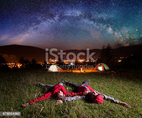 678554980istockphoto Twosome admiring the bright stars and lying on the grass 678554960