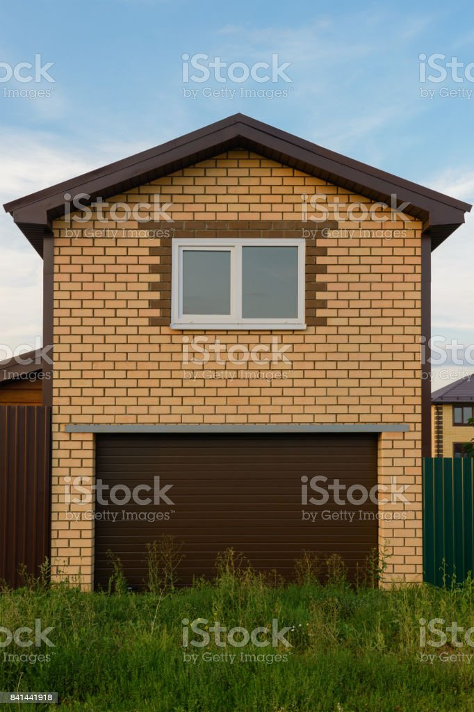 Two-storey brick garage with a window in the summer evening stock photo