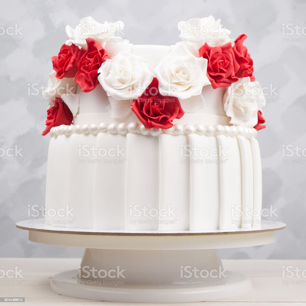 Twotiered Wedding Cake Decorated With Red And White Flowers From