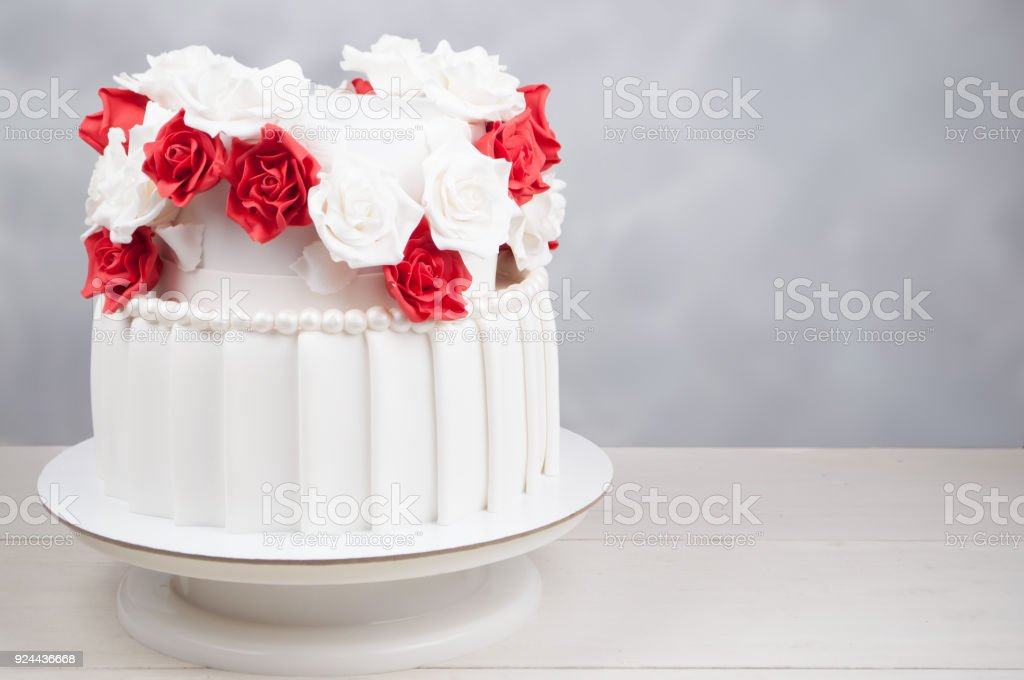 Twotiered wedding cake decorated with red and white flowers from two tiered wedding cake decorated with red and white flowers from mastic on a white mightylinksfo
