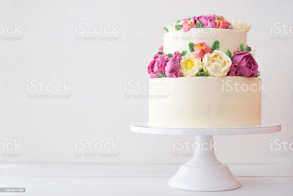 Two-tiered white wedding cake decorated with color cream flowers - Стоковые фото Астра роялти-фри