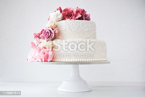 Two-tiered white wedding cake decorated with pink flowers on a white wooden background.