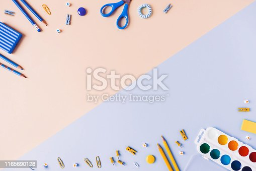 istock Two-tone background with scattered writing materials. 1165690128