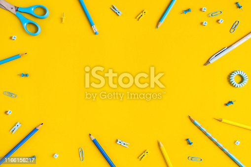 istock Two-tone background with scattered writing materials. 1166156217