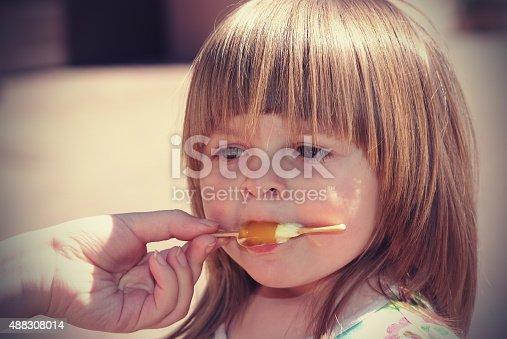 istock Two-year girl eats ice cream 488308014