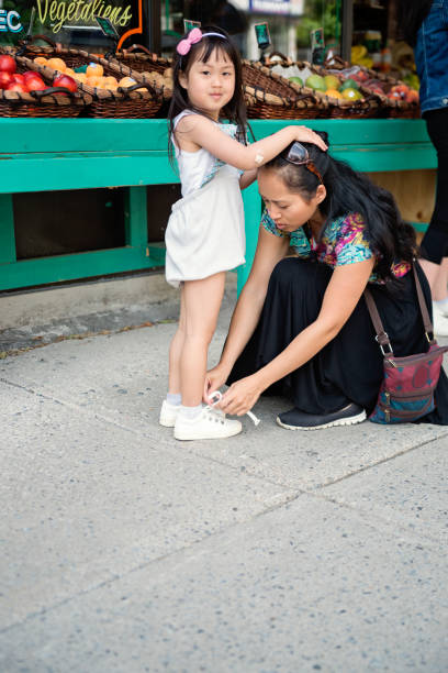 Tying a shoe outside zero waste oriented fruit and grocery store. stock photo
