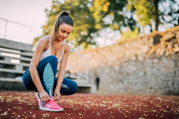 ein schnürsenkel binden - joggerin stock-fotos und bilder