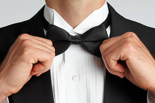 Tying Bow Tie A close up of a man in a tuxedo adjusting his bow tie. bow tie stock pictures, royalty-free photos & images