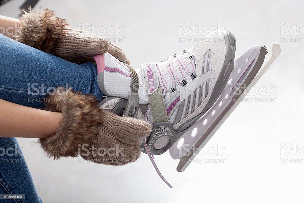 Tying laces of ice figure skates stock photo