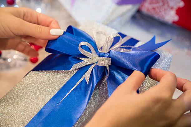 Tying ribbon on gift box. – Foto