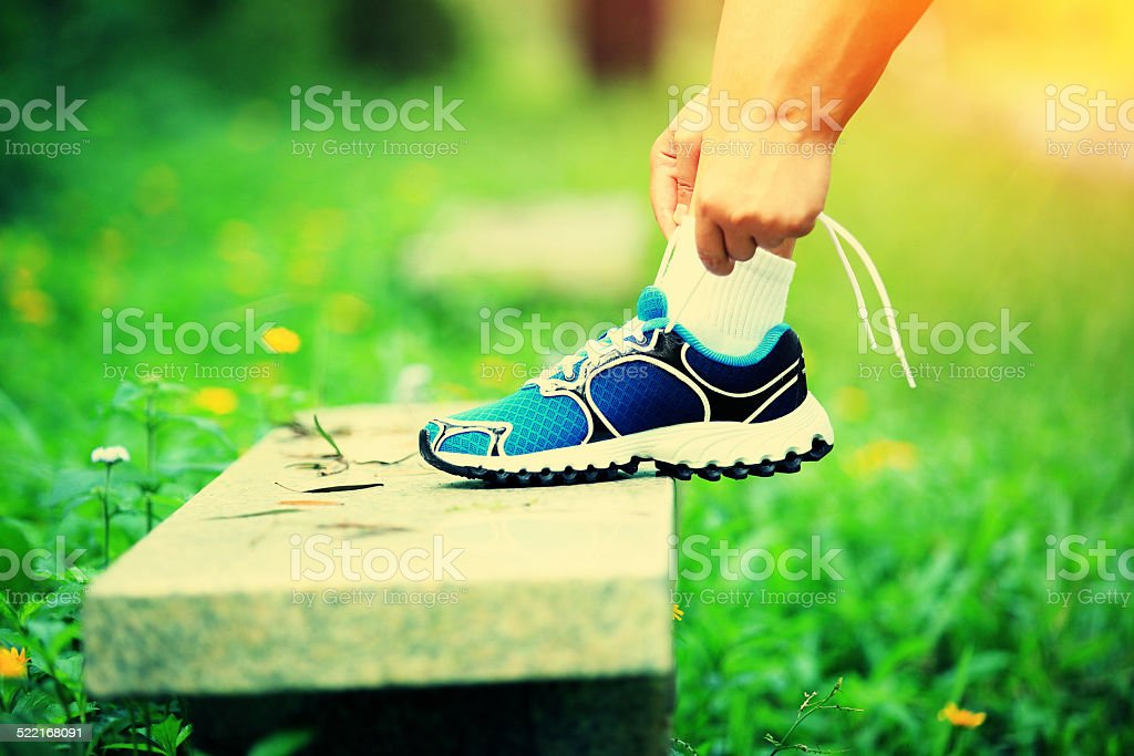 tying shoelace on stone bench in green grass stock photo