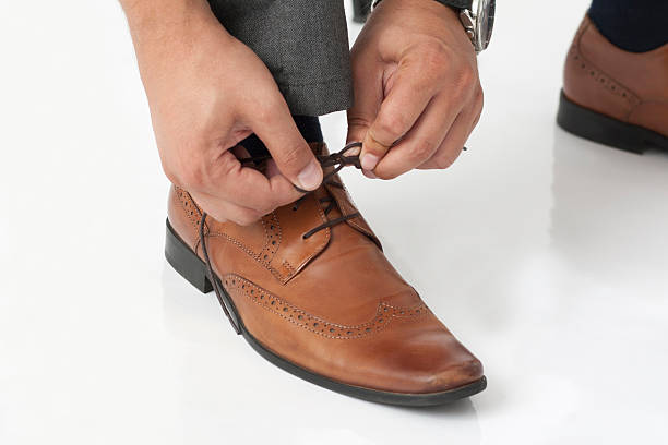 tying shoelaces - leaving partnership corporate business sitting stock photos and pictures
