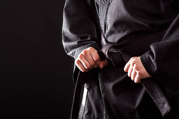 tying the knot to his black belt - martial arts stock photos and pictures