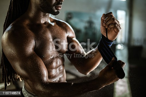 Unrecognizable black athlete tying up sports glove before weight training in a gym.