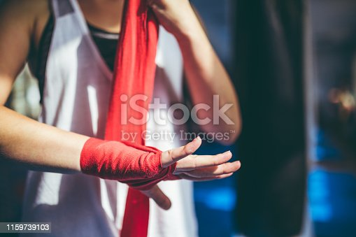 Young caucasian woman tying up sports glove and preparing for a training.