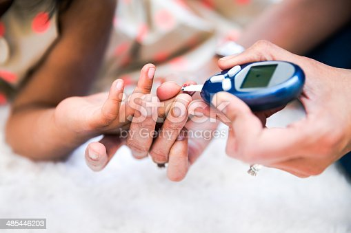 Mother is checking her daughters' diabetes by monitoring blood glucose.