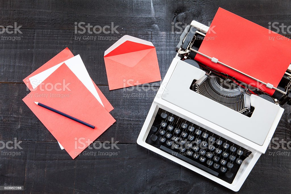 Typewriter and a red paper  on wooden background retro stock photo
