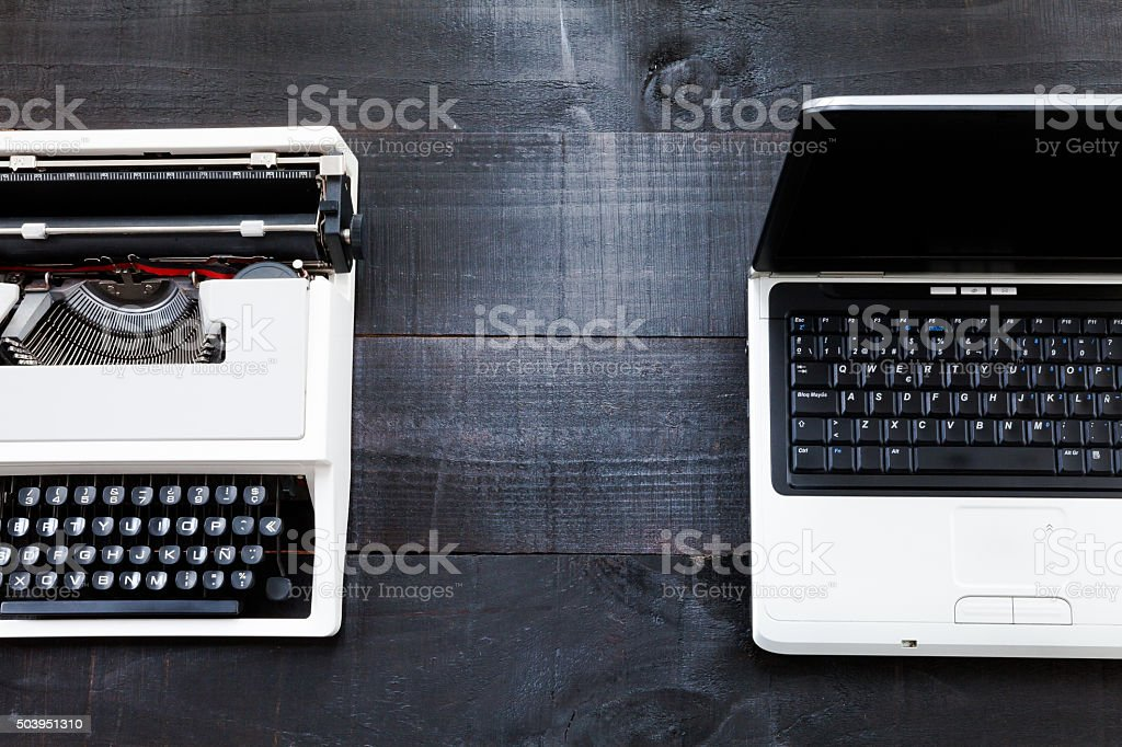 Typewriter and computer laptop on wooden background retro stock photo