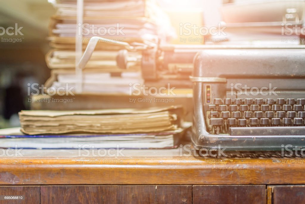 Typewriter antique vintage style with old documents or old letter for writer on wooden desk zoom in front view of typewriter, writer or editor in vintage office concept. stock photo