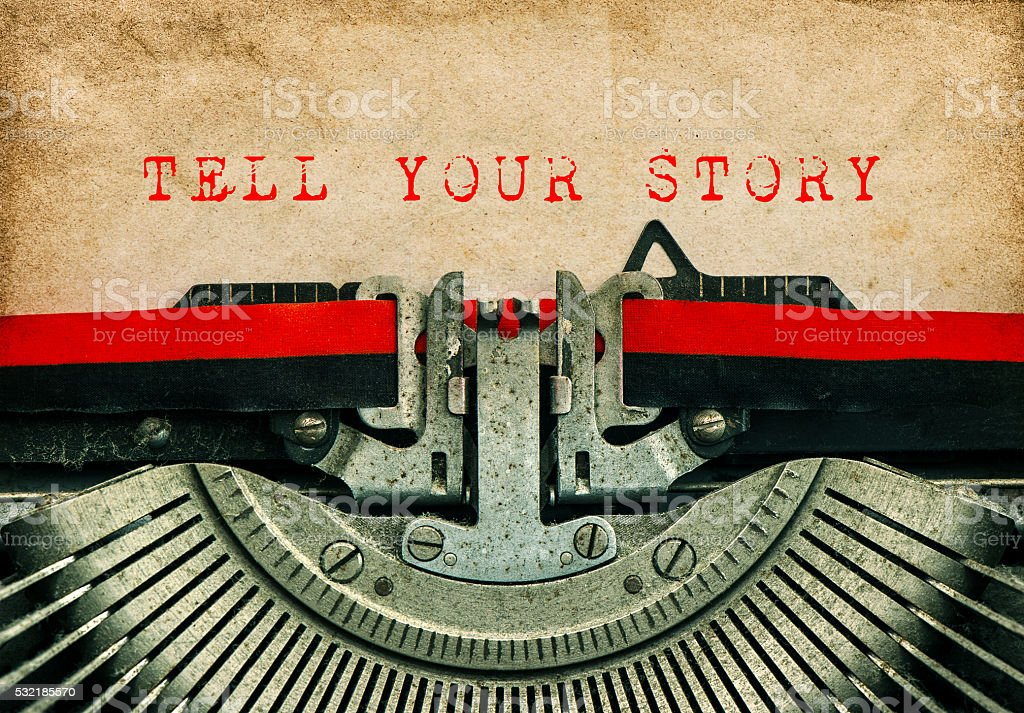 Typewriter Grungy paper background TELL YOUR STORY stock photo