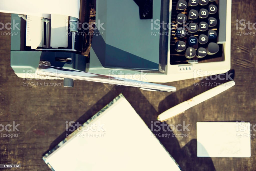 typewriter on a wooden table in the park next to glasses and a notebook on a sunny autumn day stock photo
