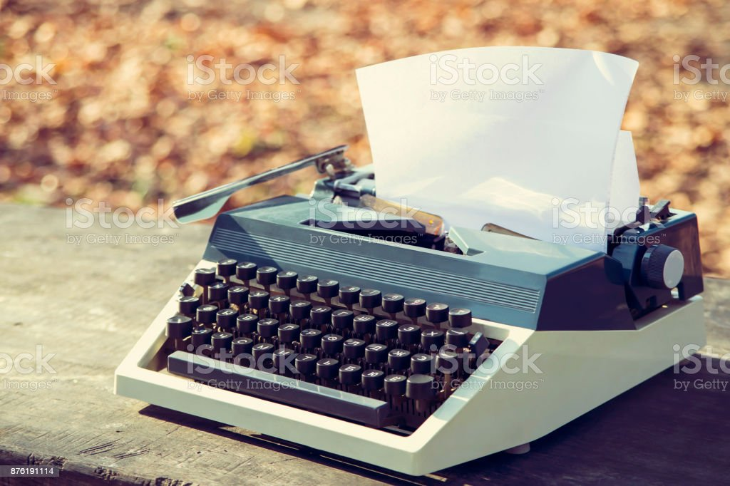 typewriter on a wooden table outdoors on a sunny autumn day stock photo