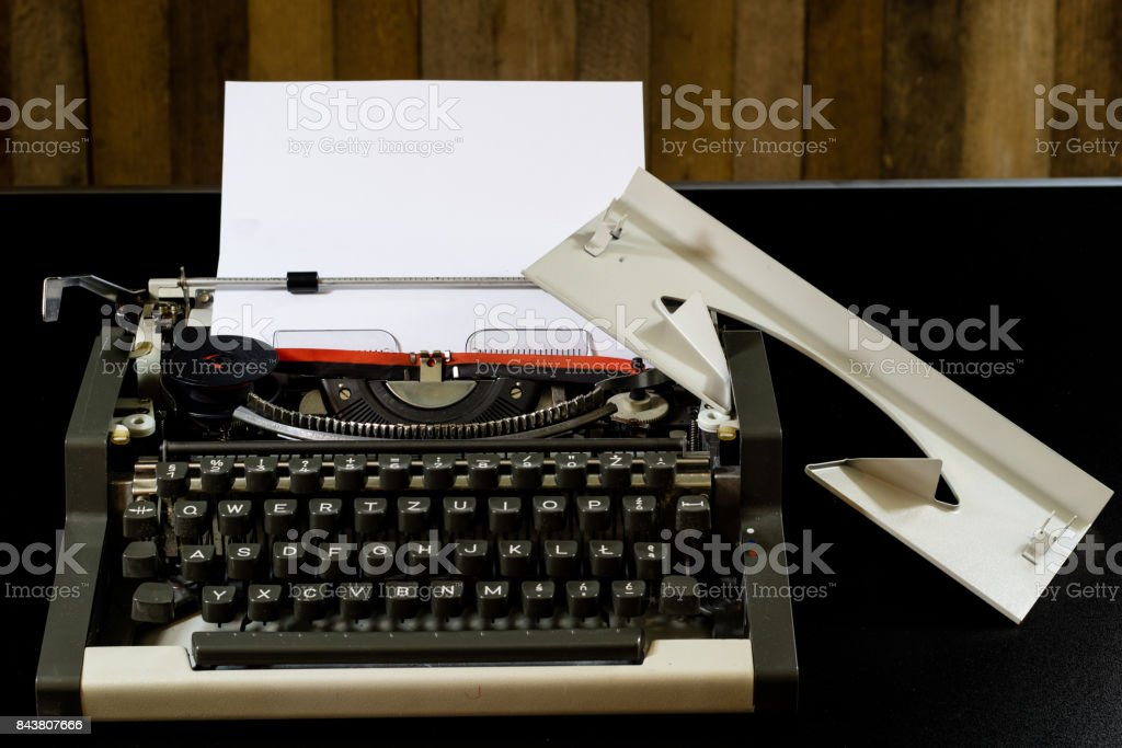 typewriter on the black table. White blank card. Wall of rough boards. black background stock photo
