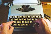 Man typing on an old typewriter