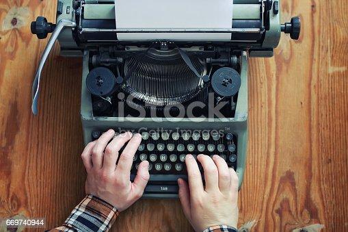 istock typewriter retro hand on wooden table 669740944