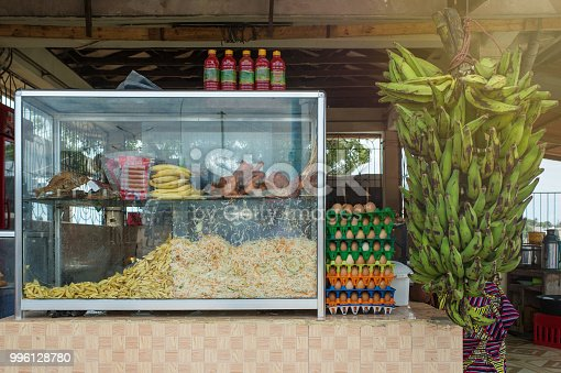Side view of a glass container filled with french fries, chopped coleslaw, fried fish and chicken pieces, vienna sausages, bananas, eggs and a bunch of green bananas hanging from the roof with chilli sauce on top Dar es Salaam Tanzania