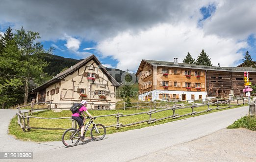A female mountainbiker is entering the village of Sporz, a typical Settlement of Graubünden, Switzerland, nearby the village of Lenzerheide. The village is part of the municipality of Vaz/Obervaz, which was definitely settled by the time of the Carolingians (750-910). Nowadays some little hotels are situated here.