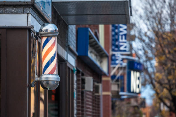 Typical American barbers pole seen in front of a barber shop of Montreal, Canada. This pole is a vintage sign indicating the presence of a male hairdresser salon. stock photo