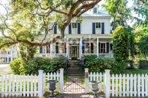 Mount Pleasant, USA - May 11, 2018: Typical American residential house building in Charleston, South Carolina area with American flag and white picket fence