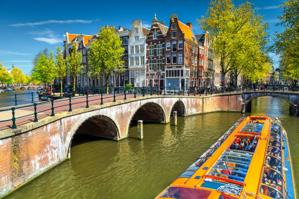 Typical Amsterdam canals with bridges and colorful boat, Netherlands, Europe stock photo