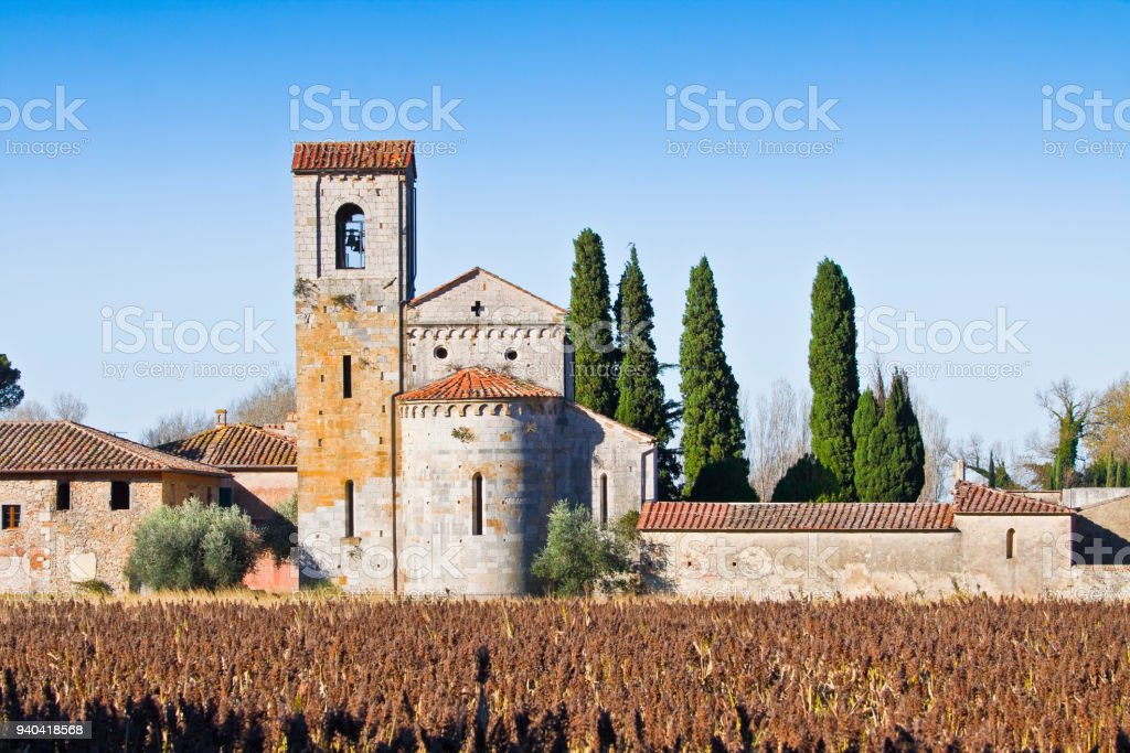 Typical ancient italian Romanesque church immersed in the Tuscany countryside near a Cemetery stock photo