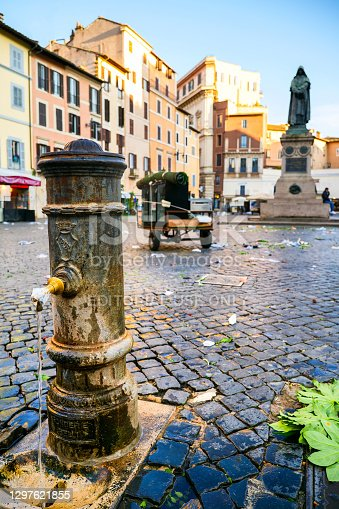 Rome, Italy, January 08 -- The statue of Giordano Bruno emerges among the market stalls in Campo de Fiori square, one of the most loved and visited places by tourists, located in the heart of Rome between Piazza Farnese and Piazza Navona. In the foreground a typical Roman fountain of drinking water. The bronze statue of the religious and philosopher Giordano Bruno, created by the sculptor Ettore Ferrari in 1889, was erected in the place where he was condemned to the stake by the Holy Inquisition in 1600. In addition to the typical daily market, Campo de Fiori is also famous for the presence of numerous restaurants, pubs and cafes. Image in high definition format.