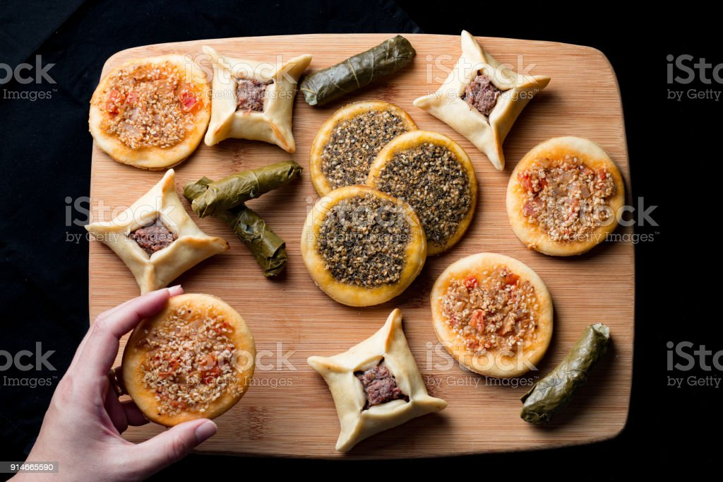 Typical arab cuisine - Sfiha - Overhead shot - woman holding one stock photo