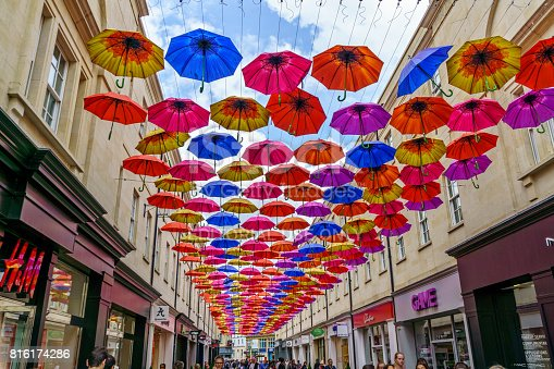 Bath, UK - July 13, 2017: Typical architecture in English city of Bath. People are pictured on the street under a canopy of colorful umbrellas