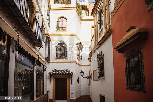 Typical architecture in Santa Cruz, an area in the city center of Seville, Spain, with narrow streets and old, colorful houses