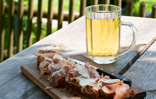 Typical Austrian finger-food with a glass of apple cider (Speckbrot und Most)