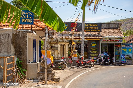 BALI, INDONESIA - December 01, 2019: Traditional Balinese Tribe Village. Cars and motorbikes drive along the street in Bali, Indonesia